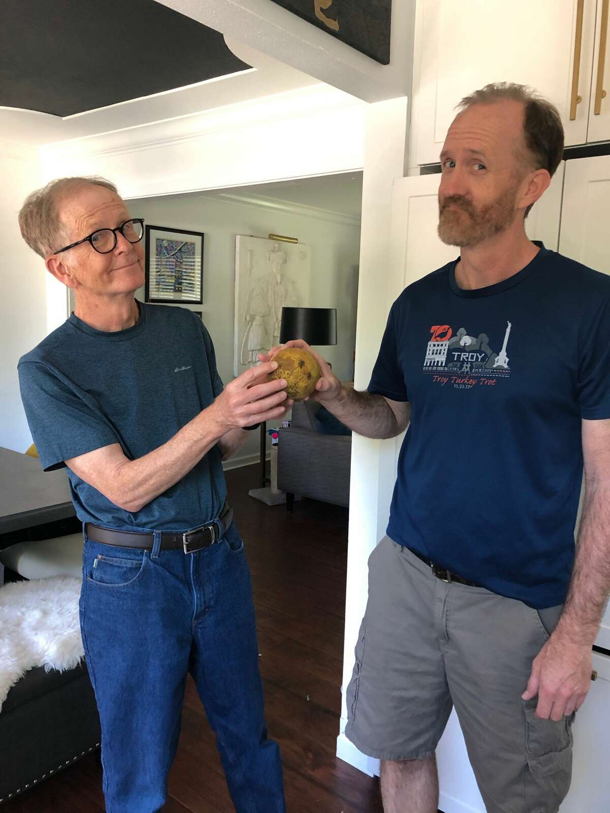 Mike Spain returns the Nerf softball to his son Jamie, who accidentally tossed the ball into a roof drain vent more than 35 years ago.