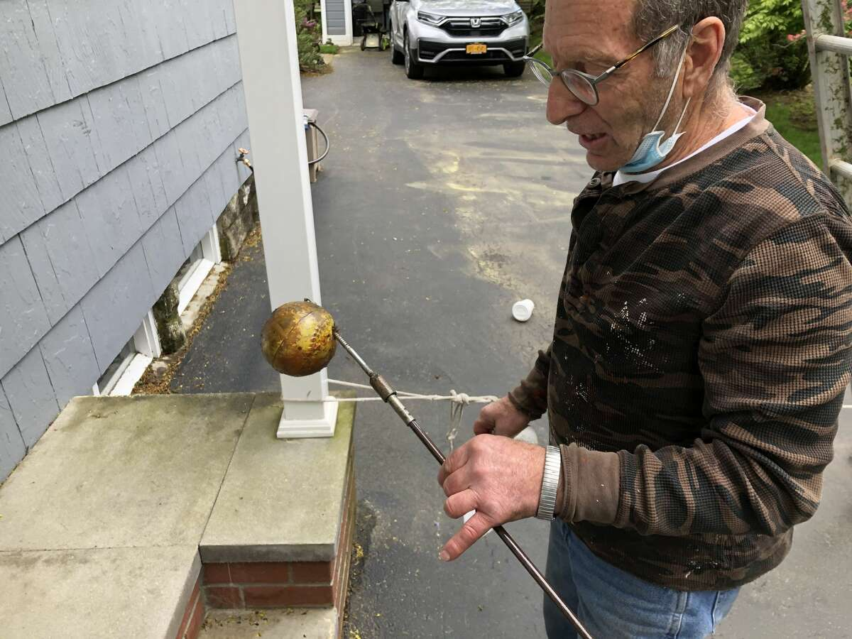 Plumber Richard Fazio holds the tool he crafted to snag a ball that was stuck in the main vent pipe for more than 35 years.