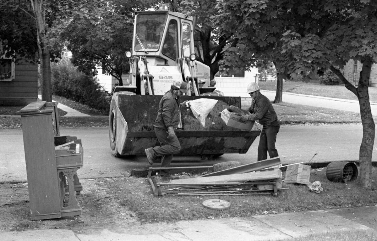 It's time for the city's annual fall trash pickup program, and city residents can unload up to one truckload per residence of debris that may have accumulated since the spring city trash pickup. Above, city employees Jack Garber (left) and Jim Polisky load a dozer full of trash parked on a curb. The photo was published in the News Advocate on Oct. 6, 1981. (Manistee County Historical Museum photo)