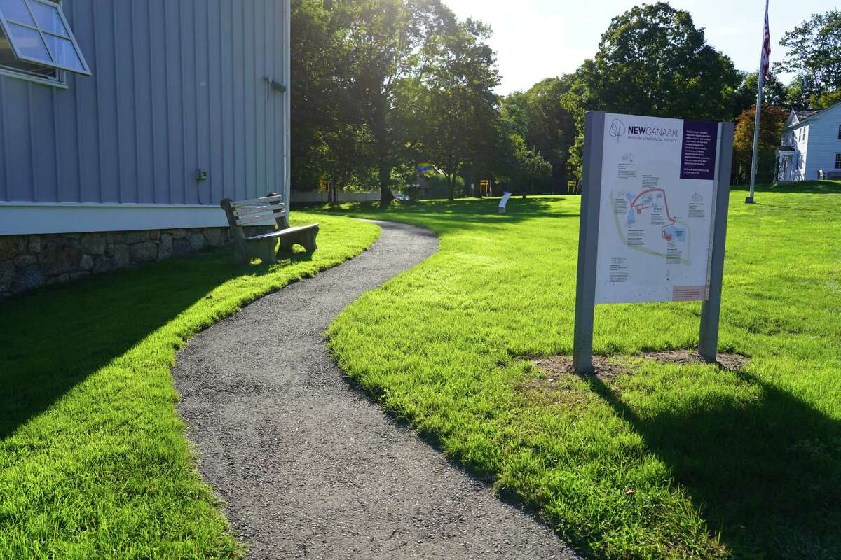 A historic trail tells 250 years of New Canaan history as it winds around the antique buildings on campus of the New Canaan Museum and Historical Society. Five placards share the details of the Cody Drug store, the Silliman House, the Tool Museum, John Rogers' Studio and general New Canaan history. The photo was taken Oct. 4, 2021.