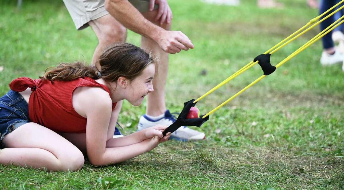 Emma Nicoletti, 9, prepares to sling an apple.