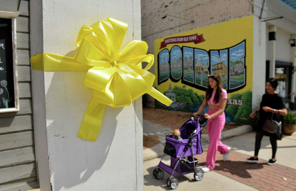 Charlotte and Maribel Patton, along with their dogs CoCo and BooBoo, walk past the yellow ribbons displayed prominently on Main Street in Boerne to remember the 13 U.S. service members who were killed at the Kabul airport in late August and to keep up hope for the Americans who are still there.
