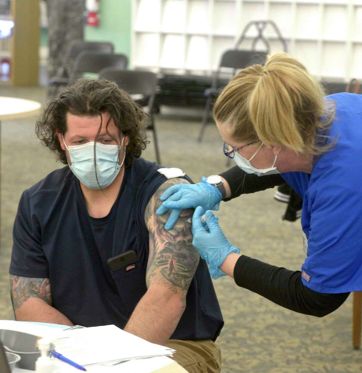 EMT Eugenia McGovern, right, from Griffin Health, administers the first shot of Moderna vaccine to Anthony Capirichio, of Danbury, who was a walk-in to the COVID-19 vaccine clinic held in the Danbury Public Library on Friday, April 30, 2021, in Danbury, Conn. The clinic is part of a partnership between the state, Federal Emergency Management Agency (FEMA) and the federal government.