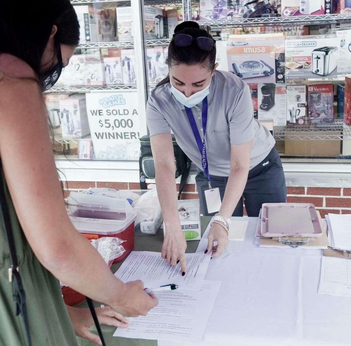 Fernanda Araujo, a nurse with the Ridgefield Visiting Nurse Association, explains COVID-19 vaccine information at CTown Supermarket in Danbury. Tuesday, June 22, 2021