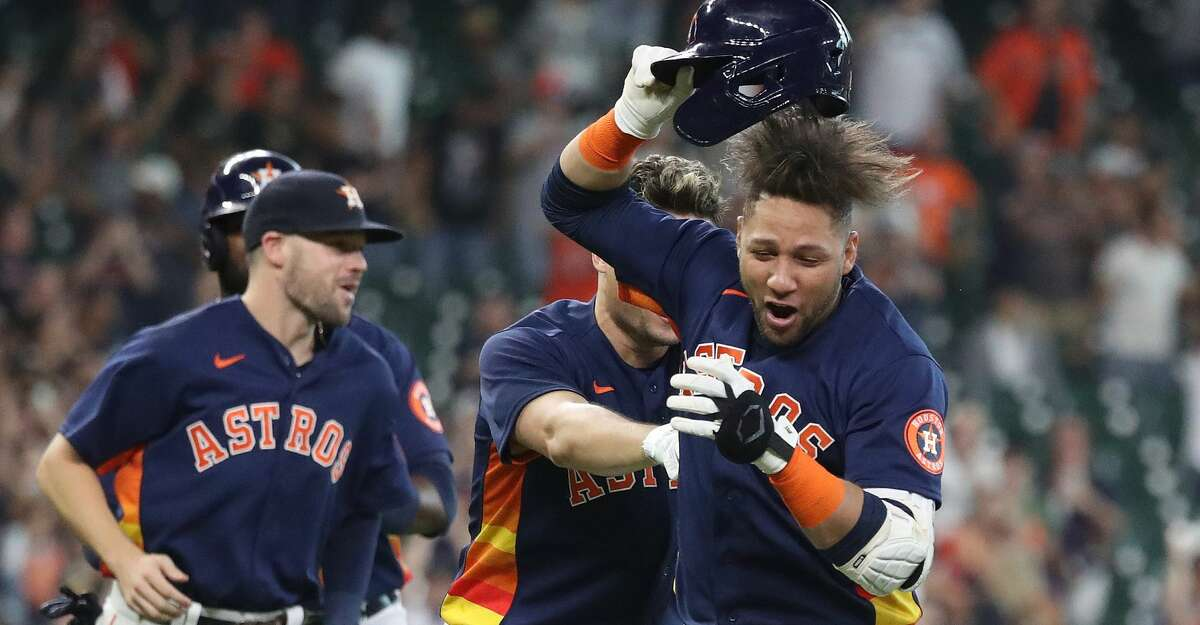 Houston Astros Yuli Gurriel (10) is mobbed by teammates after his single off of Oakland Athletics relief pitcher Lou Trivino scored Jason Castro for the game winning run during the ninth inning of an MLB baseball game at Minute Maid Park, Sunday, October 3, 2021, in Houston.
