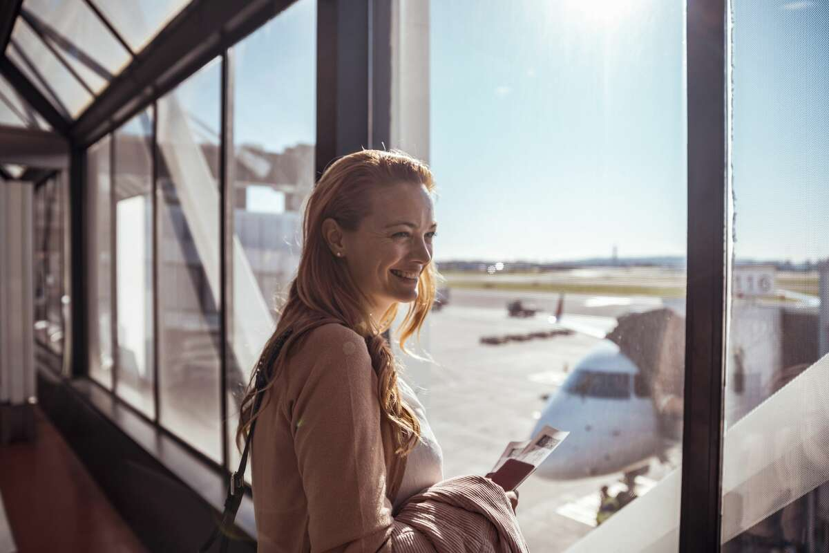 A young woman waiting to board the airplane at the airport