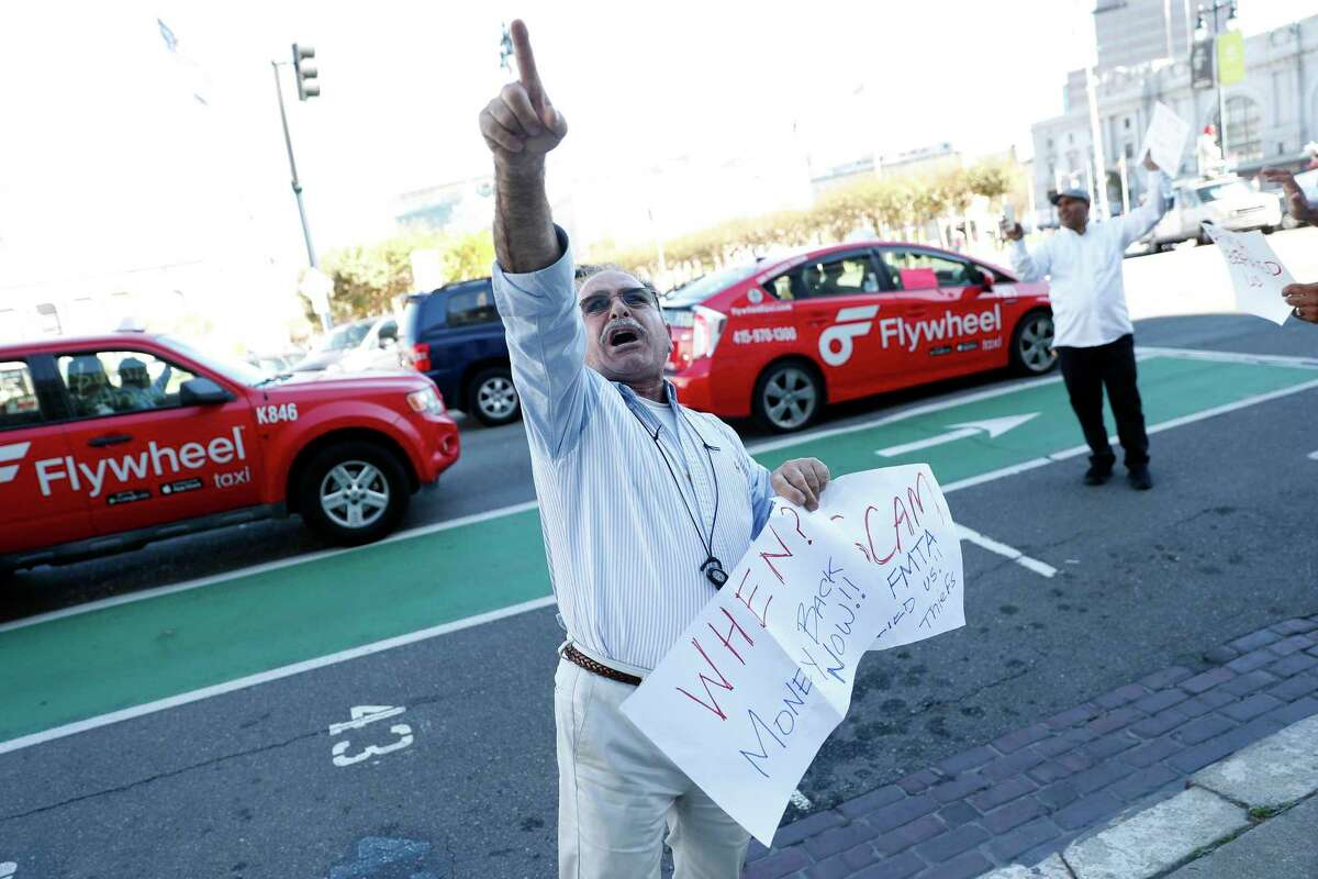 Taxi driver Alan Khani points towards the San Francisco City Hall as he joins protest in 2019.