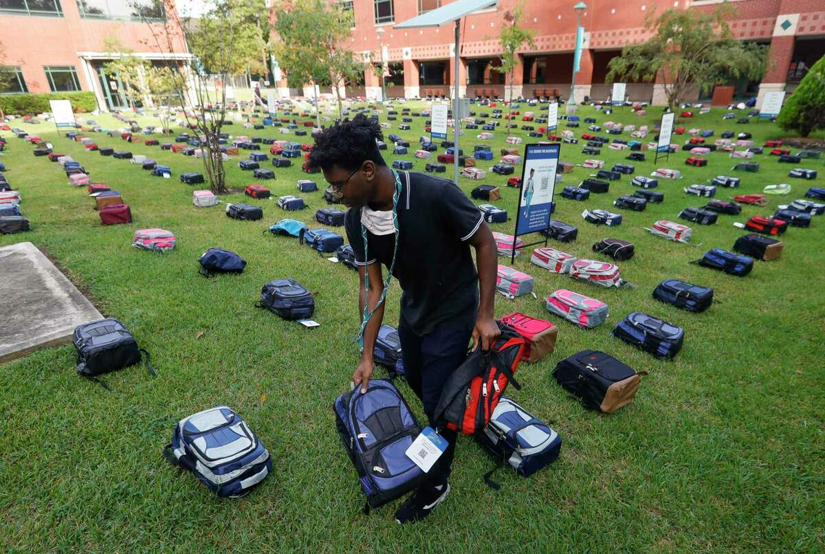 Kallel Joseph helps places backpacks as part of the Send Silence Packing display at Lone Star College - Montgomery, Monday, Oct. 4, 2021, in Conroe. The traveling display of 1,000 backpacks were displayed on campus containing personal items, stories & pictures of students who have lost their battles with mental health as a result of suicide.