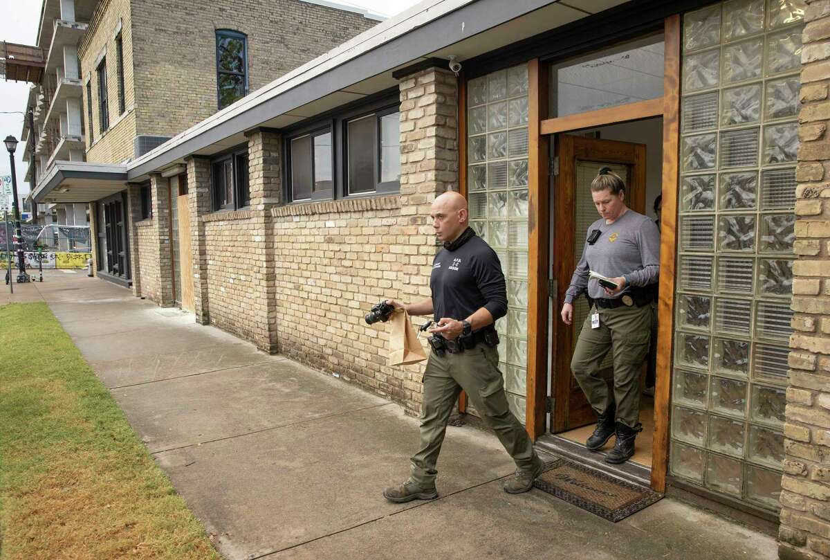 Austin Fire Department arson investigators Lt. Steven Silverthorn, left, and Lt. Kelly Gall investigate at the Travis County Democratic Party office on East 6th Street in Austin, Texas, on Wednesday, Sept. 29, 2021, after someone threw a rock and an incendiary device into the building. (Jay Janner/Austin American-Statesman via AP)