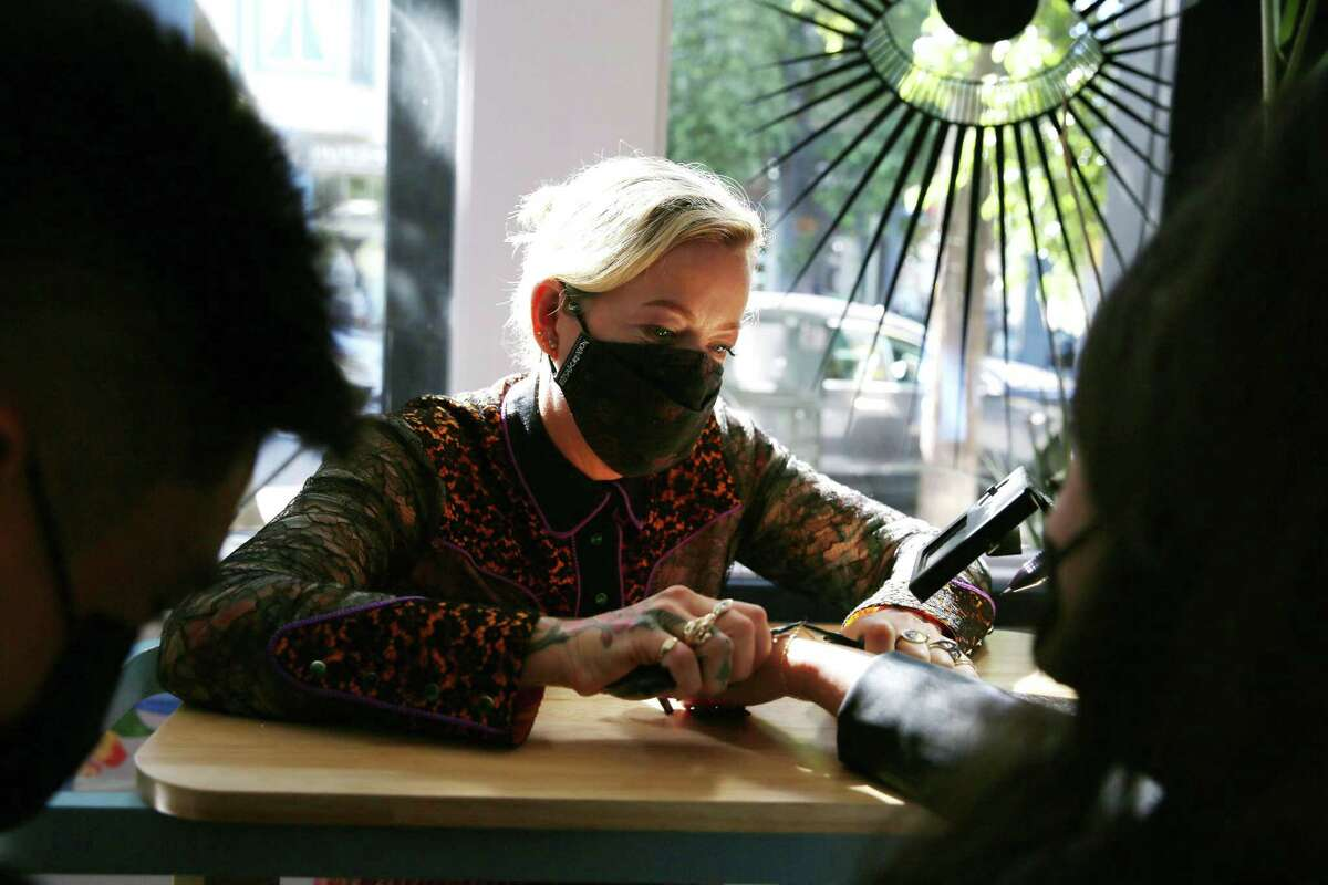 Marie McCarthy, Fiat Lux owner, custom fits a bracelet onto the wrist of Rachel Goltiao of Vallejo before fusing it around her wrist at Fiat Lux on Sept. 29 in San Francisco.