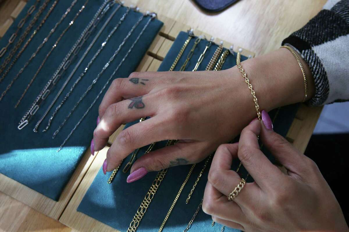 Customer Lily Law drapes a bracelet chain over her wrist to decide which selection to choose before having it fused around her wrist at Fiat Lux on Sept. 29 in San Francisco.
