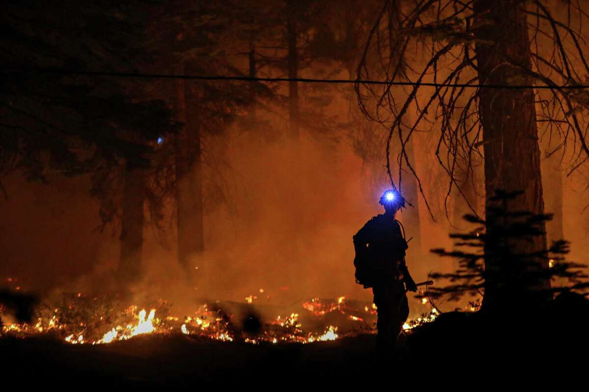 A firefighter monitors a large blaze a part of the Caldor Fire near a home near Strawberry, Calif. on Sunday, Aug. 29, 2021.