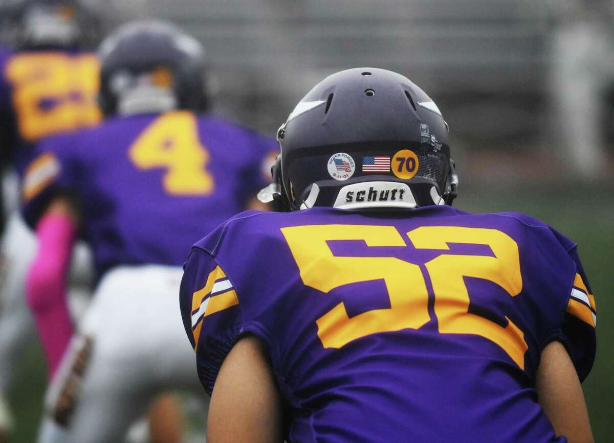 Westhill's Jordan Napolitano wears a number 70 decal on his helmet in memory of teammate Jordan Martinez on Monday, in the team's first game since his death, at Westhill High School in Stamford. Martinez, a senior, died in a single car crash in Greenwich on Sept. 25. He was honored by fans and teammates at Westhill's game against Amity on Monday.