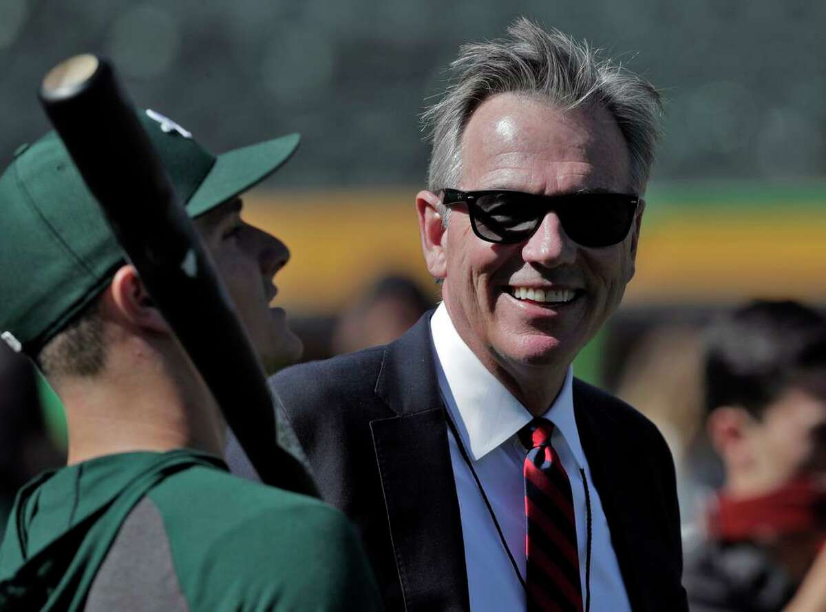 Billy Beane chats wtih Matt Chapman (26) before the Oakland Athletics played the Tampa Bay Rays at the Oakland Coliseum in the Wild Card playoff game in Oakland, Calif., on Wednesday, October 2, 2019.