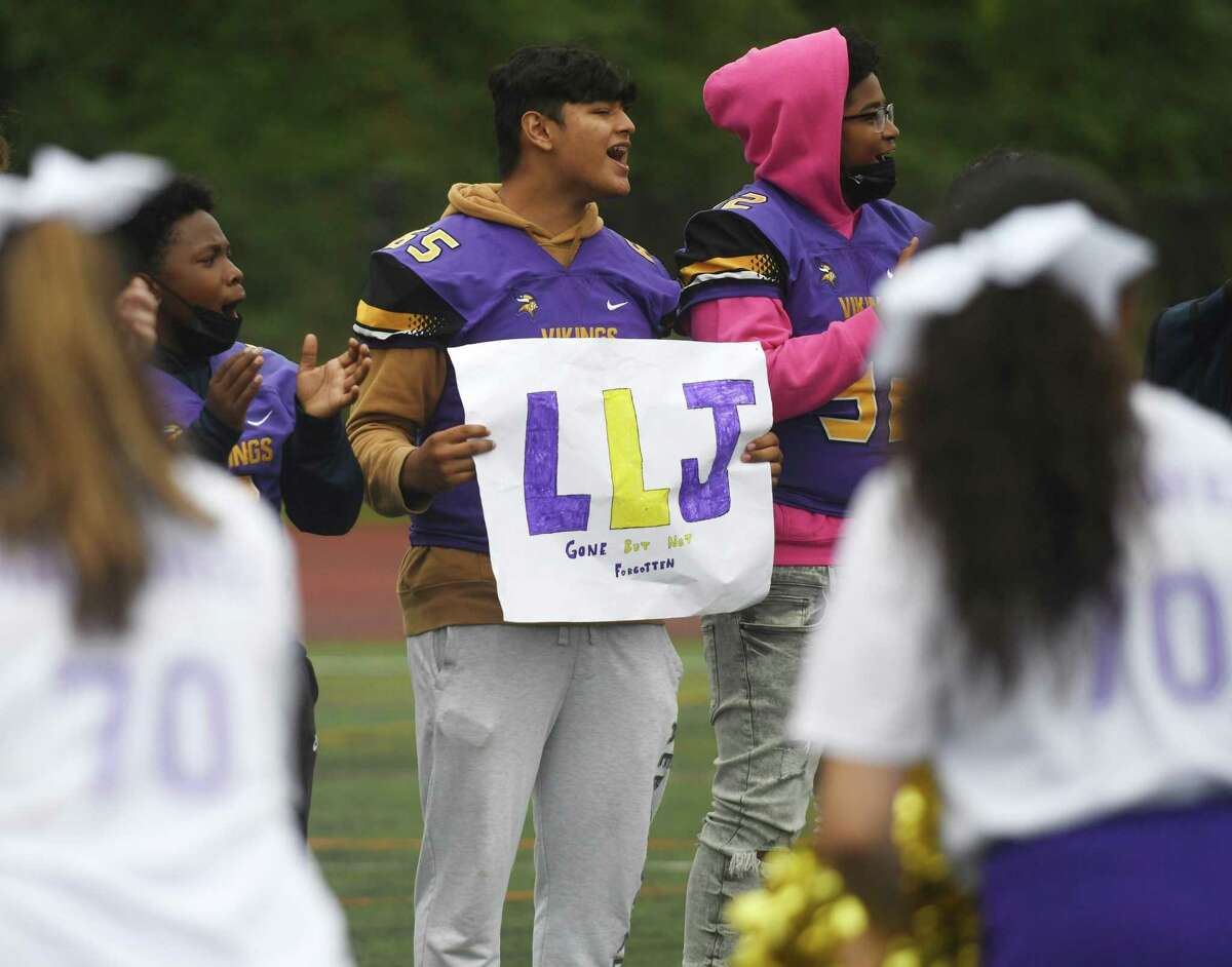 """Jose Rivas Perez holds a sign standing for """"Long Live Jordan"""" in the football team's first game since the death of teammate Jordan Martinez at Westhill High School in Stamford, Conn. Monday, Oct. 4, 2021. Martinez, a senior, died in a single car crash in Greenwich on Sept. 25. He was honored by fans and teammates at Westhill's game against Amity on Monday, the team's first game since his death."""