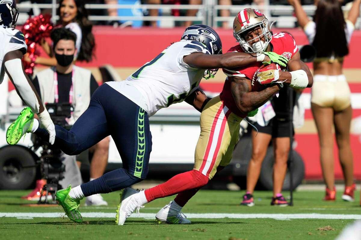 San Francisco 49ers' Trenton Cannon, right, is tackled by Seattle Seahawks' DeeJay Dallas an NFL football game in Santa Clara, Calif., Sunday, Oct. 3, 2021. (AP Photo/Tony Avelar)