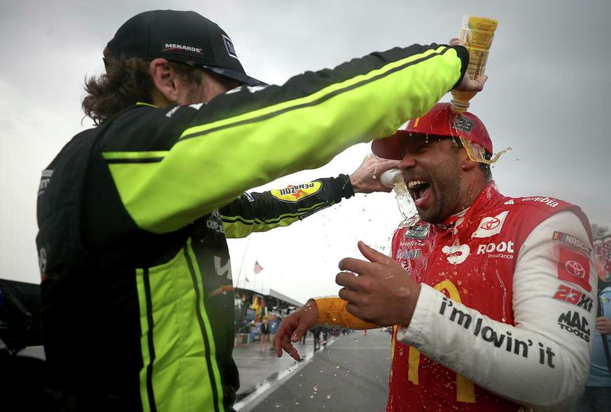 Bubba Wallace (right), celebrates with Ryan Blaney after winning the rain-shortened NASCAR playoff race.