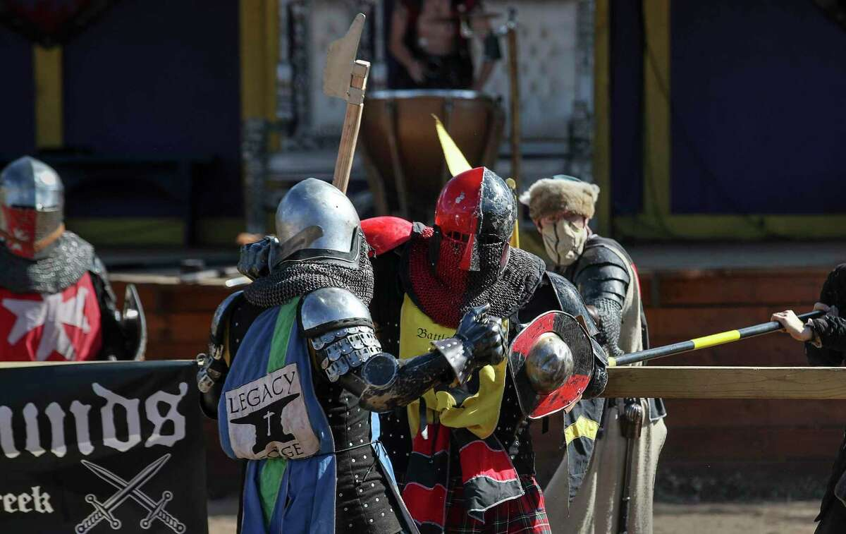 """Anthony Bernabeo, front right, competes against another knight in armored combat in the arena on Saturday, Nov. 21, 2020, at the Texas Renaissance Festival in Todd Mission, Texas. Another fighter said Bernabeo was """"a silverback gorilla who can box."""" By day, he is a Harris County deputy sheriff, and he competes in armored combat at the festival."""