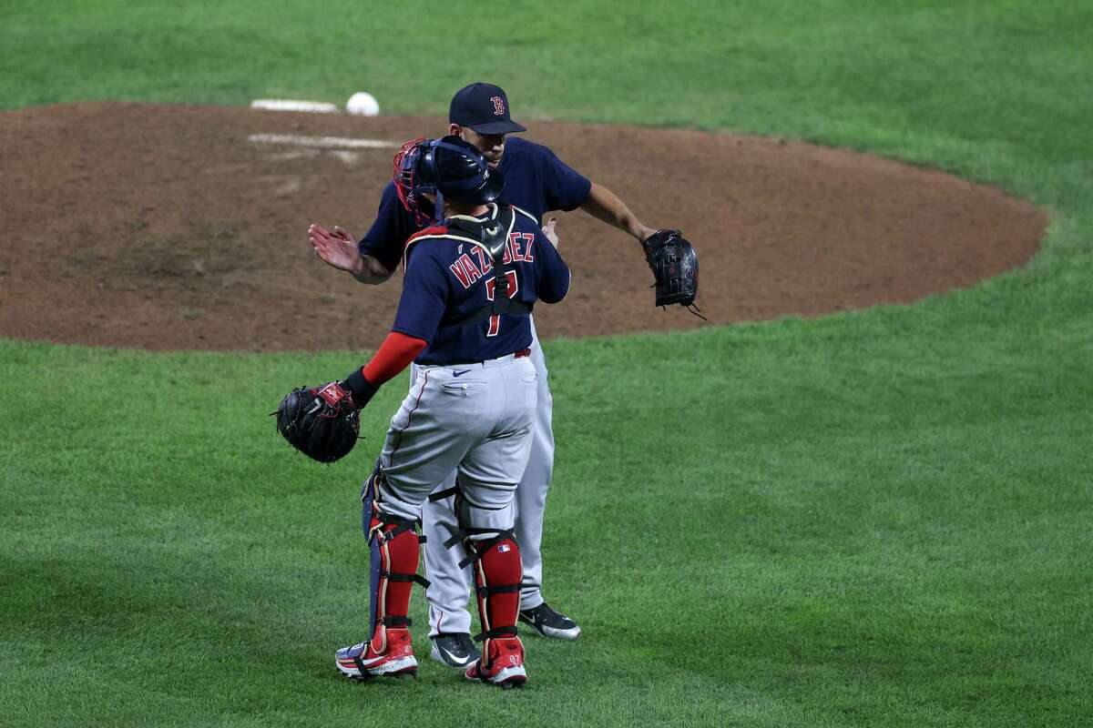 Matt Barnes #32 and Christian Vazquez #7 of the Boston Red Sox celebrate their 6-0 win over the Baltimore Orioles at Oriole Park at Camden Yards.