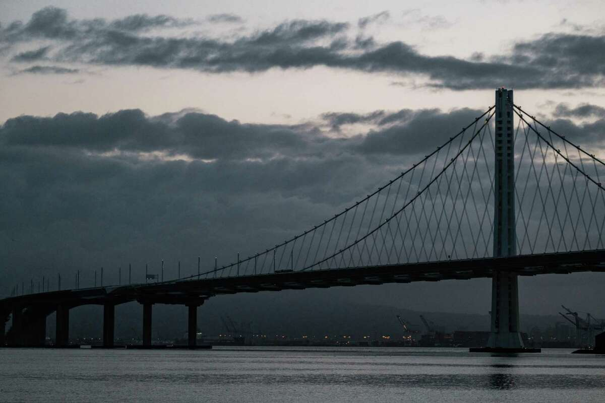 The Bay Bridge is seen with large clouds looming over the East Bay as seen from Treasure Island on January 27, 2021. Cloudy skies, cooler temperatures and possibly some rain are in the forecast for this week.