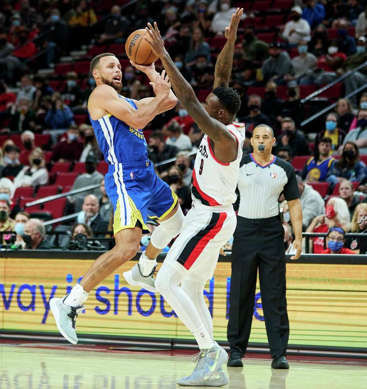 Warriors guard Stephen Curry shoots over the Blazers' Nassir Little during the preseason game Monday in Portland.