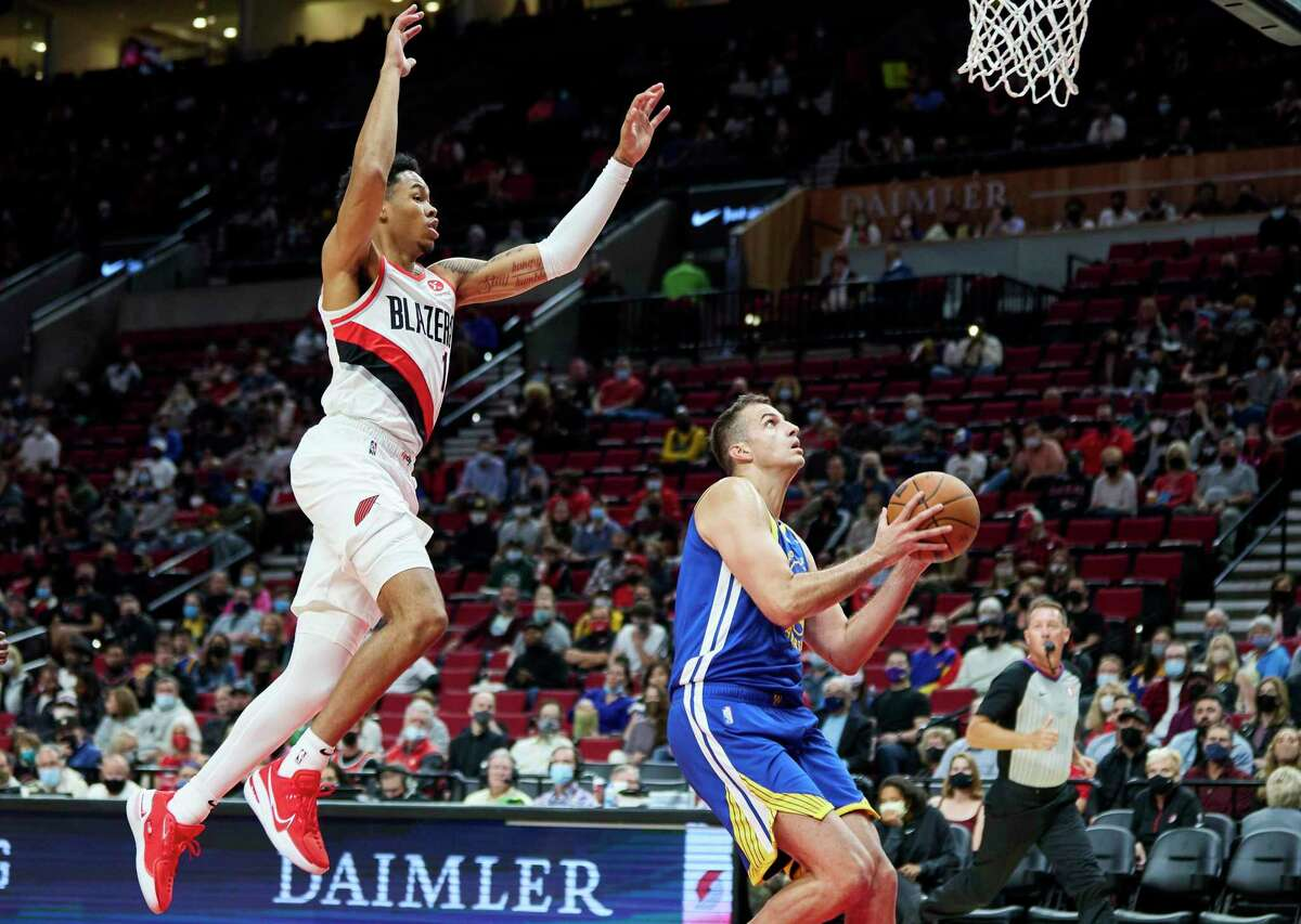 Golden State Warriors forward Nemanja Bjelica, right, shoots in front of Portland Trail Blazers guard Anfernee Simons during the first half of a preseason NBA basketball game in Portland, Ore., Monday, Oct. 4, 2021. (AP Photo/Craig Mitchelldyer)
