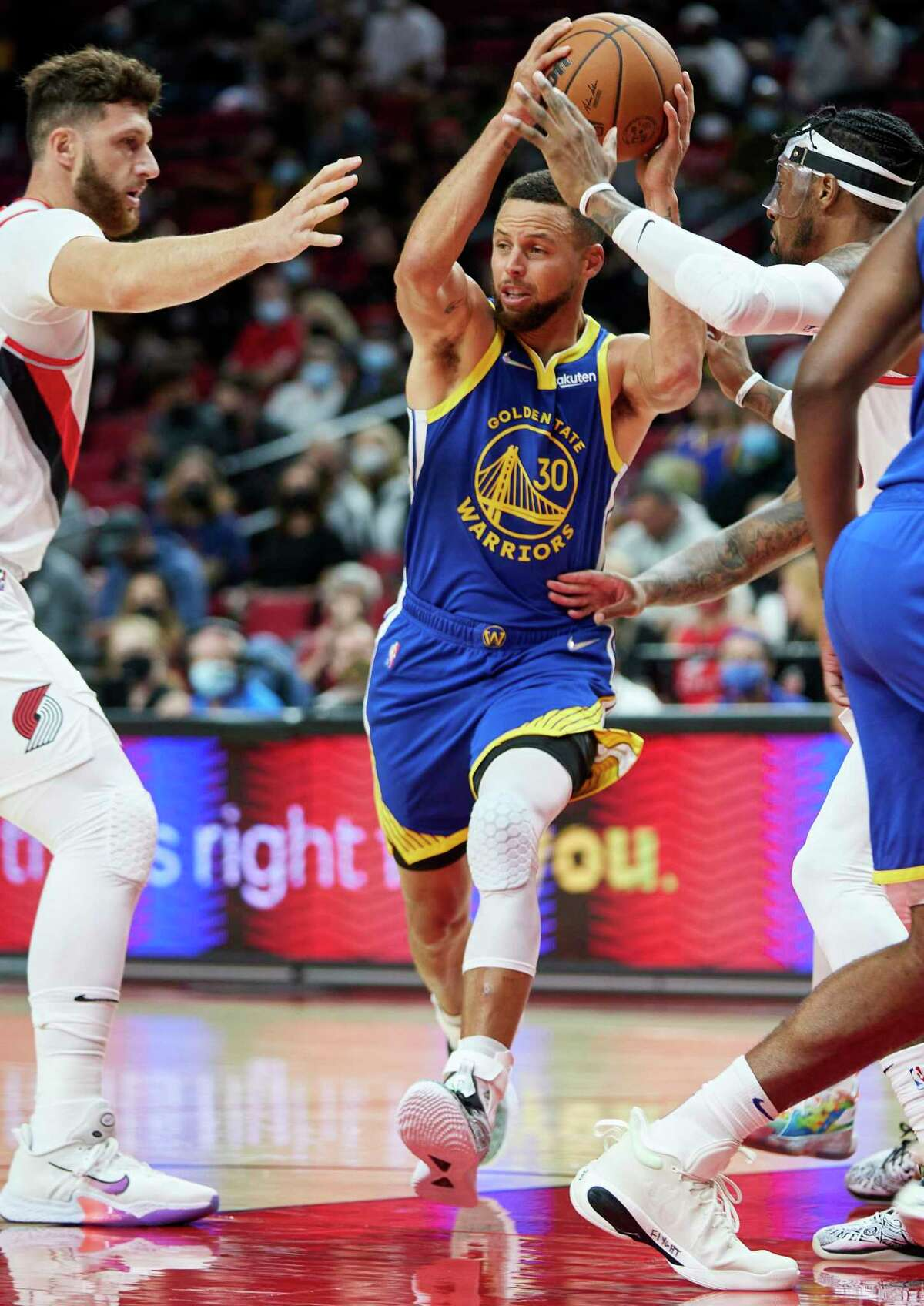 Golden State Warriors guard Stephen Curry, center, drives to the basket between Portland Trail Blazers center Jusuf Nurkic, left, and forward Robert Covington, right, during the first half of a preseason NBA basketball game in Portland, Ore., Monday, Oct. 4, 2021. (AP Photo/Craig Mitchelldyer)