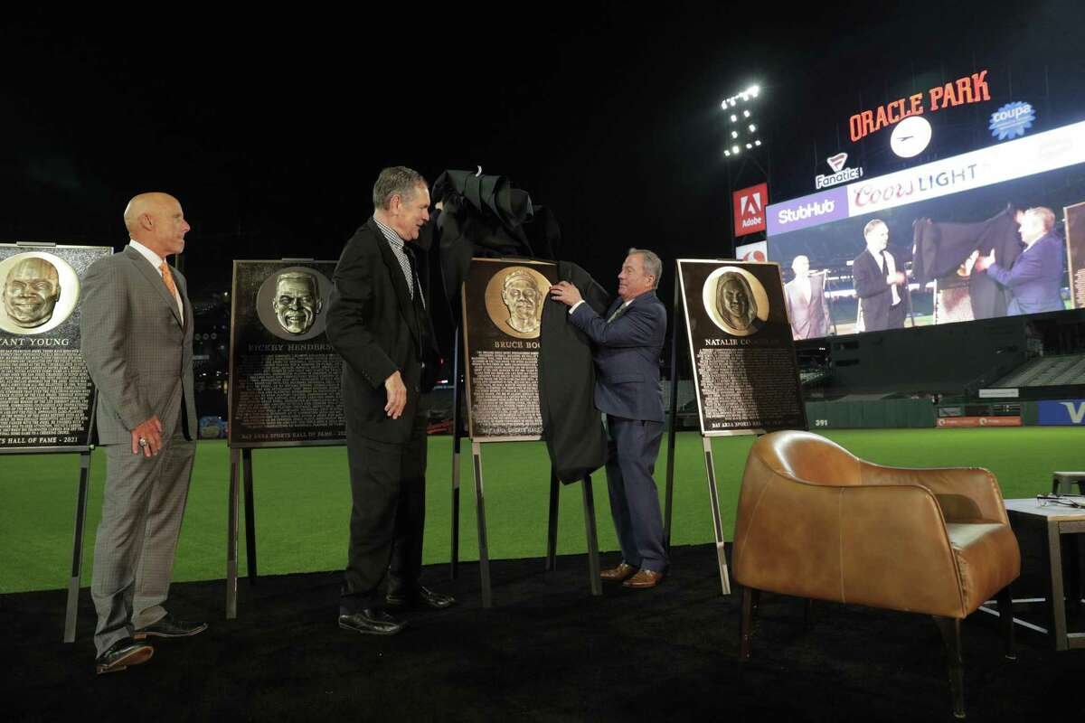 Former Giants manager Bruce Bochy unveils his plaque with Tim Flannery snd Mario Alioto on stage during the Bay Area Sports Hall of Fame induction ceremony at Oracle Park in San Francisco, Calif., on Monday, October 04, 2021.
