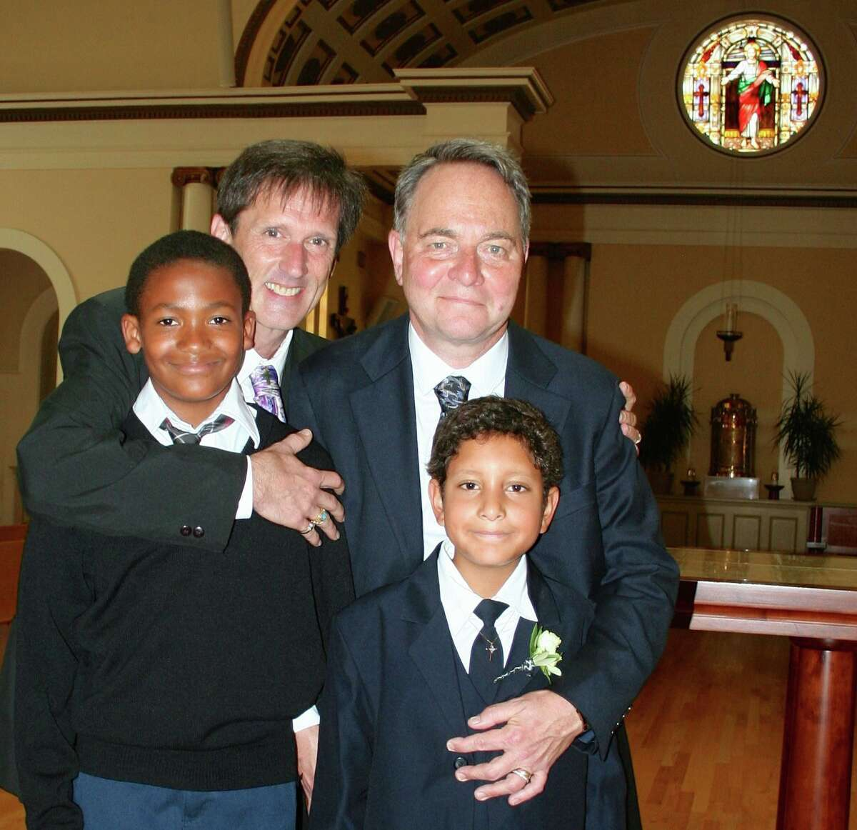 Kevin Fisher-Paulson (right) and husband Brian, with sons Zane (left) and Aidan at Most Holy Redeemer Church in San Francisco.