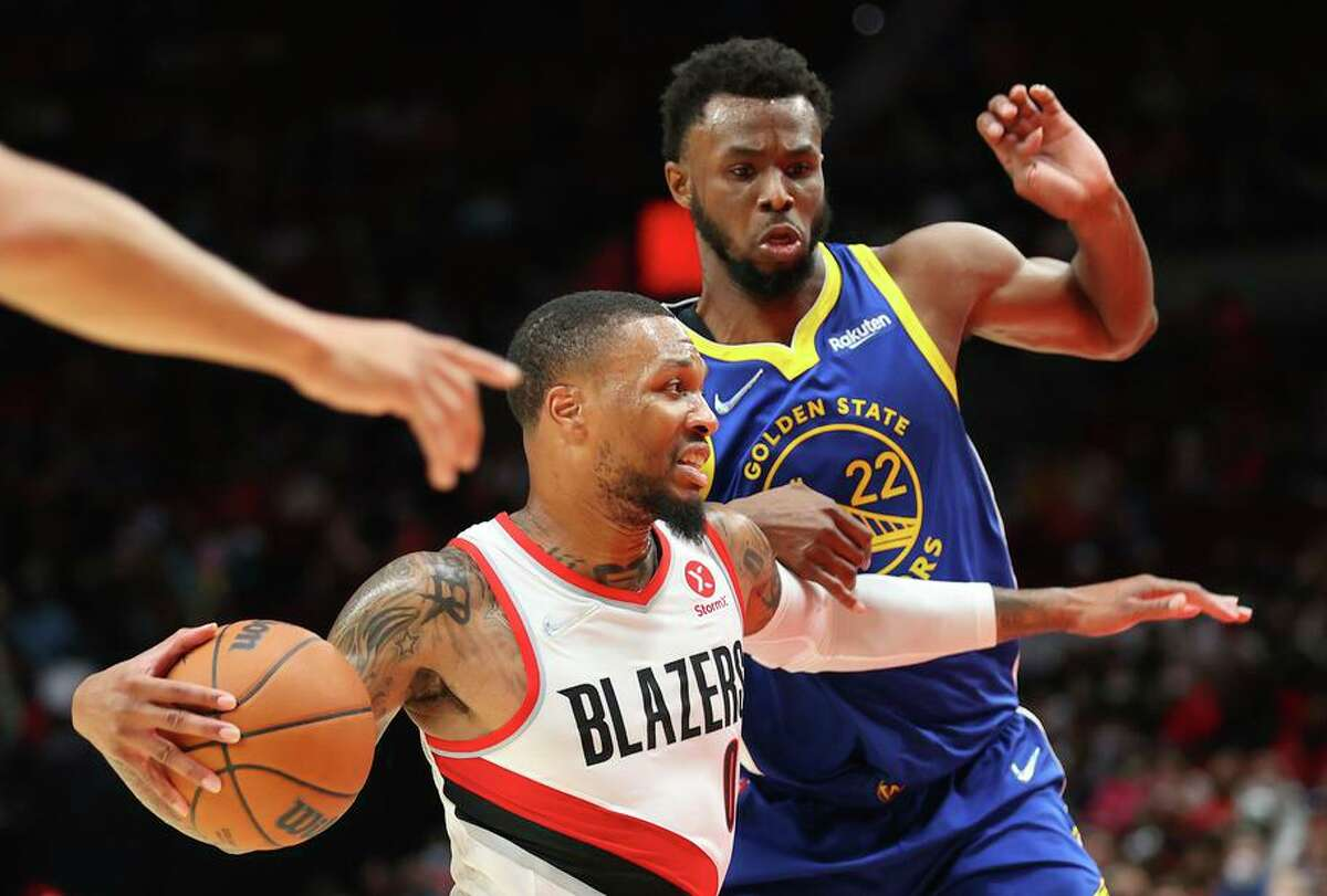PORTLAND, OREGON - OCTOBER 04: Damian Lillard #0 of the Portland Trail Blazers works towards the basket against Andrew Wiggins #22 of the Golden State Warriors in the second quarter during the preseason game at Moda Center on October 04, 2021 in Portland, Oregon. NOTE TO USER: User expressly acknowledges and agrees that, by downloading and or using this photograph, User is consenting to the terms and conditions of the Getty Images License Agreement. (Photo by Abbie Parr/Getty Images)