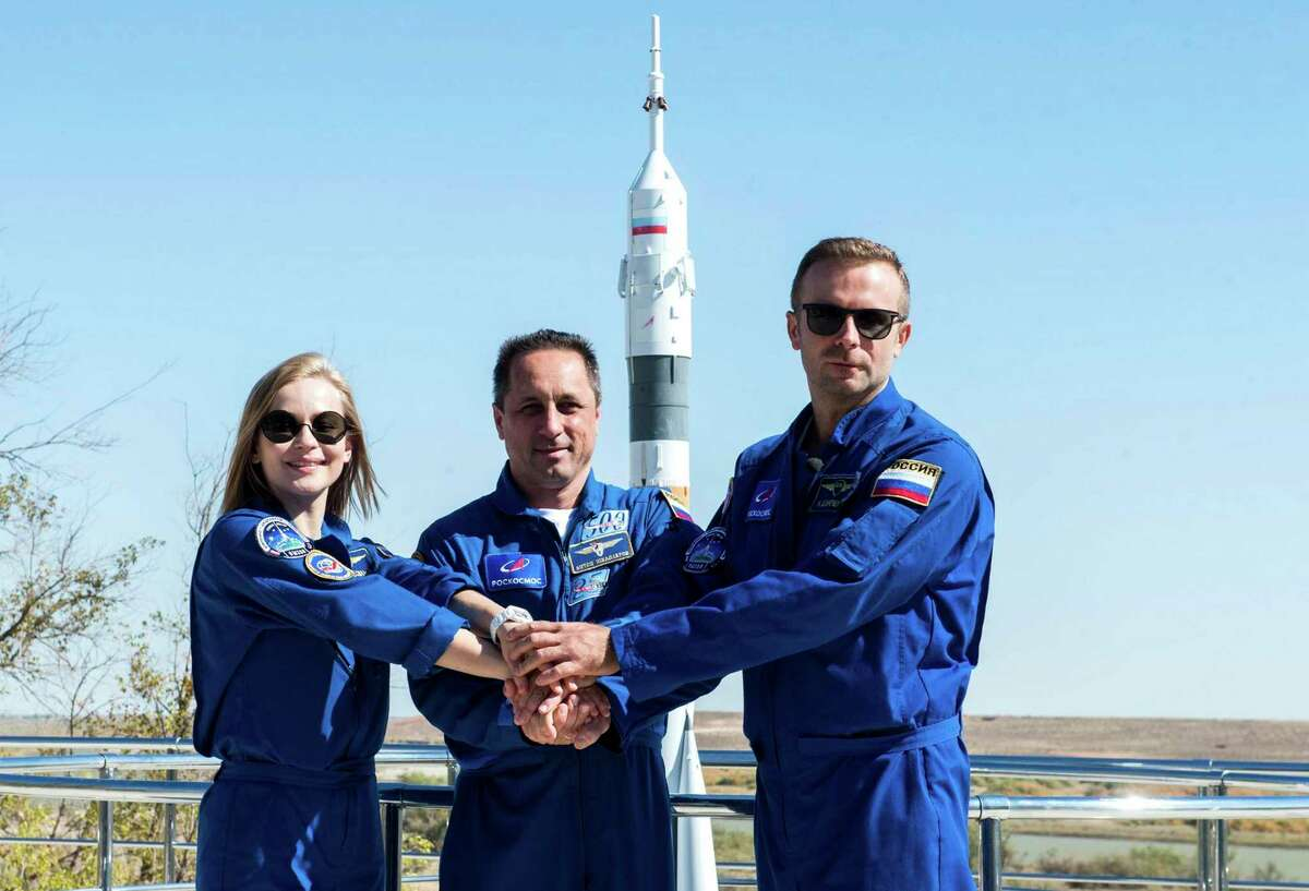 In this handout photo released by Roscosmos, actress Yulia Peresild, left, director Klim Shipenko, right, and cosmonaut Anton Shkaplerov at the Russian launch facility in the Baikonur Cosmodrome, Kazakhstan, Monday, Sept. 27, 2021.