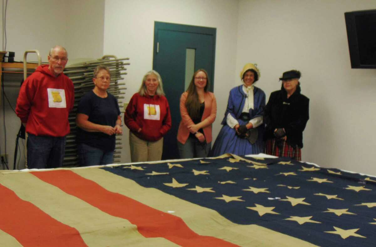 Members of the Lake County Historical Society, along with Melissa Fish from Gov. Gretchen Whitmer's office, view the American flag presented to Baldwin by Gov. Baldwin in 1872 (Star photo/Shanna Avery)