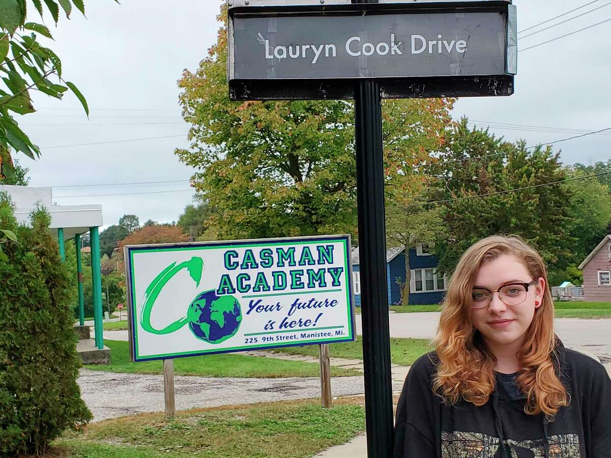 Lauryn Cook,the CASMAN Academy Student of the Month, poses next to the sign that names the school driveway in her honor. (Courtesy photo)