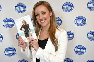 """HENDERSONVILLE, TN - OCTOBER 27: Co-Host Megan Alexander shows her new book """"Faith in the Spotlight"""" during the 2016 Inspirational Country Music Association Awards at Trinity Music City on October 27, 2016 in Hendersonville, Tennessee. (Photo by Rick Diamond/Getty Images for Inspirational Country Music Association)"""
