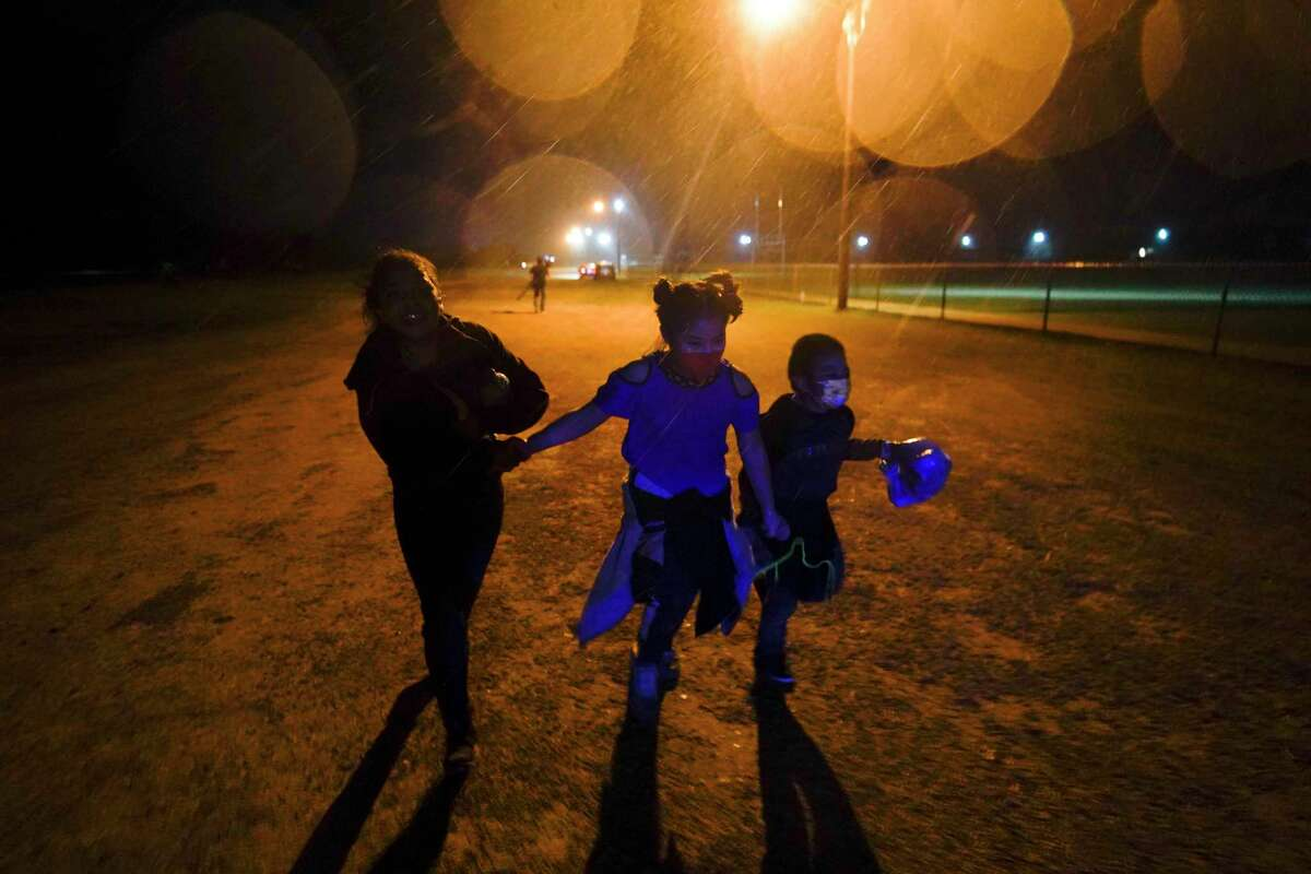 Three young migrants run in the rain at a facility in Roma. Despite concerns about the treatment of migrant children in emergency shelters, a visit to one in Pecos was reassuring.