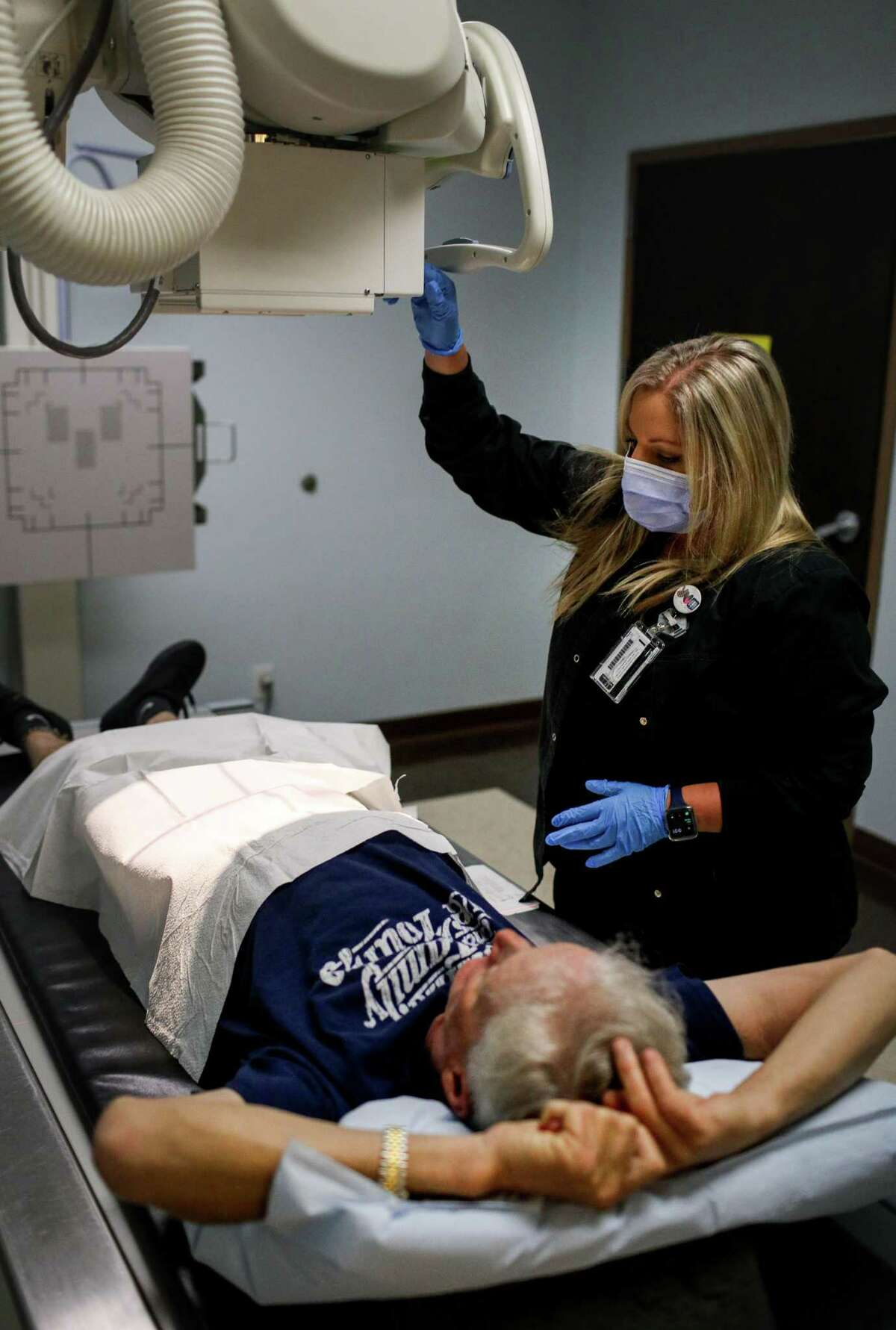 Tommy Goodwin, left, a professional stuntman who had his pelvis surgically repaired after an accident, prepares to have X-rays done by Tiffany Bryant, a radiology technician, Wednesday, Sept. 15, 2021, at an outpatient clinic in Houston.