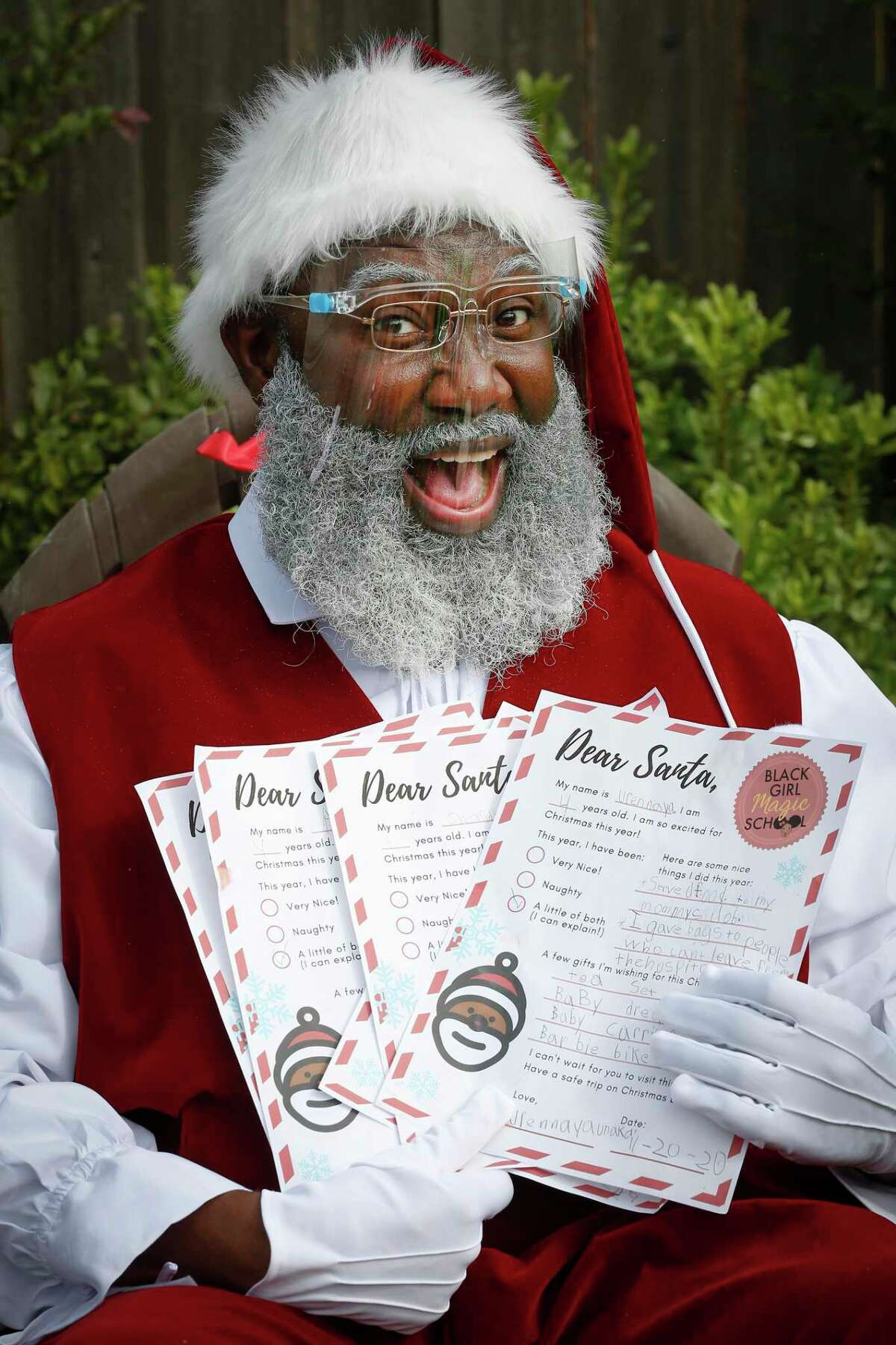 Black Santa (aka Kelvin Douglas) holds a stack of Christmas Wish list from girls at the Black Girl Magic School Saturday, Nov. 21, 2020, in Houston.