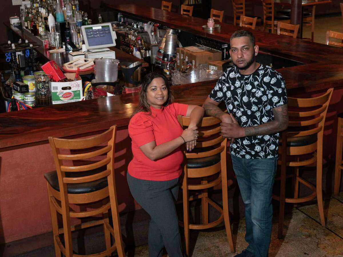 Tropics restaurant owners Mavis Diaram and her husband Vakanand Diaram stand in their restaurant on Tuesday, Oct, 5, 2021 in Schenectady, N.Y. Some in the city are calling for the Guyanese-West Indian restaurant to be shut down after a recent deadly shooting in the parking lot of the establishment.