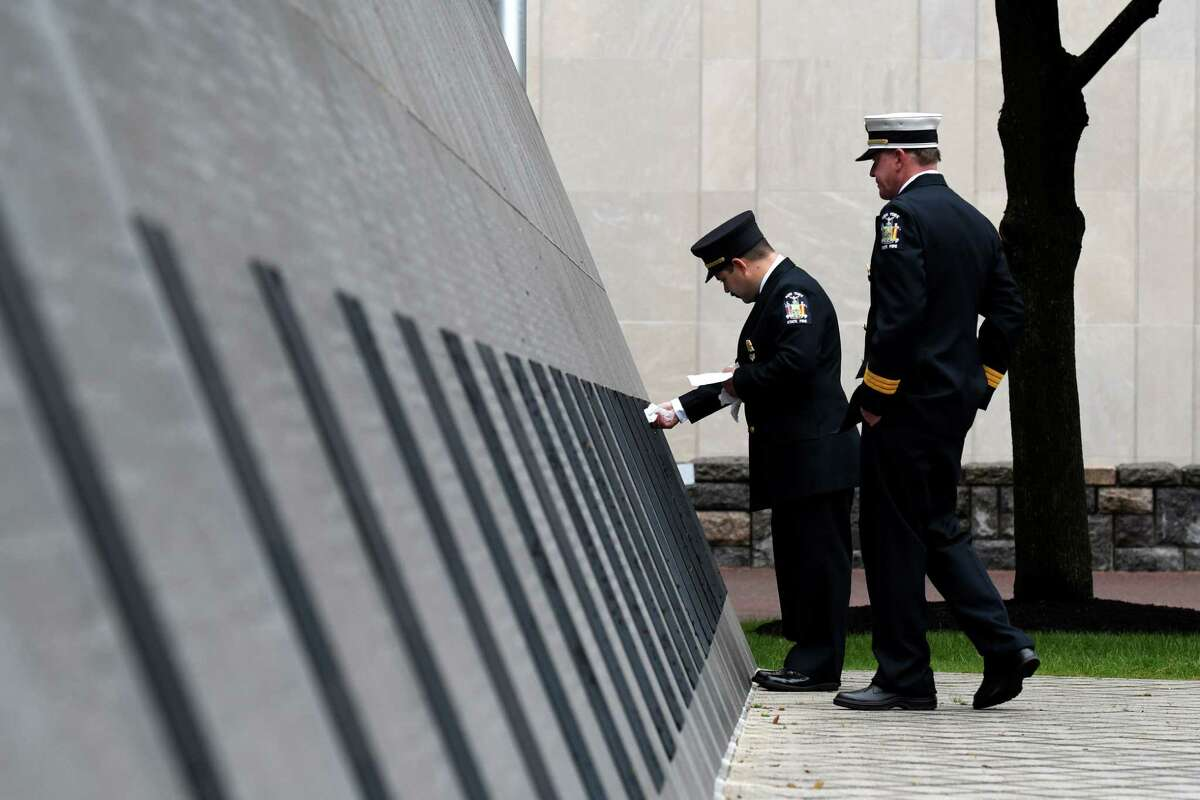 Joe Marini, a fire protection specialist with New York State Fire, dries the names of firefighters who were recently added to the New York State Fallen Firefighters Memorial on Tuesday, Oct. 5, 2021, at Empire State Plaza in Albany, N.Y. Twenty-four names were added to wall this year, including Donald G. Thomas of the Ballston Spa Fire Department. Last year?•s ceremony honoring twenty-one fallen firefighters was postponed due to the pandemic. Michael G. Miles of Albany County with the NYS Office of Fire Prevention and Control was added in 2020.