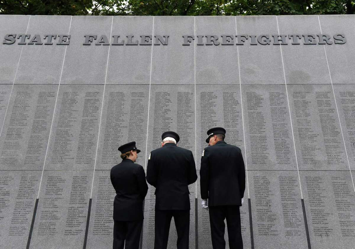 Members of Schuyler Hose Company from Schuylerville remember a fallen brother while attending the New York State Fallen Firefighters Memorial on Tuesday, Oct. 5, 2021, during the annual ceremony at Empire State Plaza in Albany, N.Y. Twenty-four names were added to wall this year, including Donald G. Thomas of the Ballston Spa Fire Department. Last year?•s ceremony honoring twenty-one fallen firefighters was postponed due to the pandemic. Michael G. Miles of Albany County with the NYS Office of Fire Prevention and Control was added in 2020.