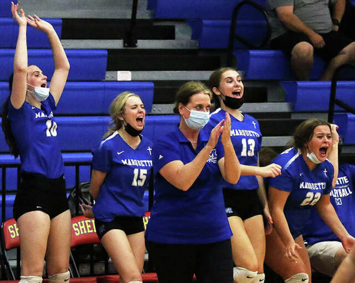 Marquette Catholic coach Sue Heinz applauds her team while Explorers on the bench celebrate match point in an August victory over Gillespie in the Roxana Tournament. The Explorers got their 21st win Monday.