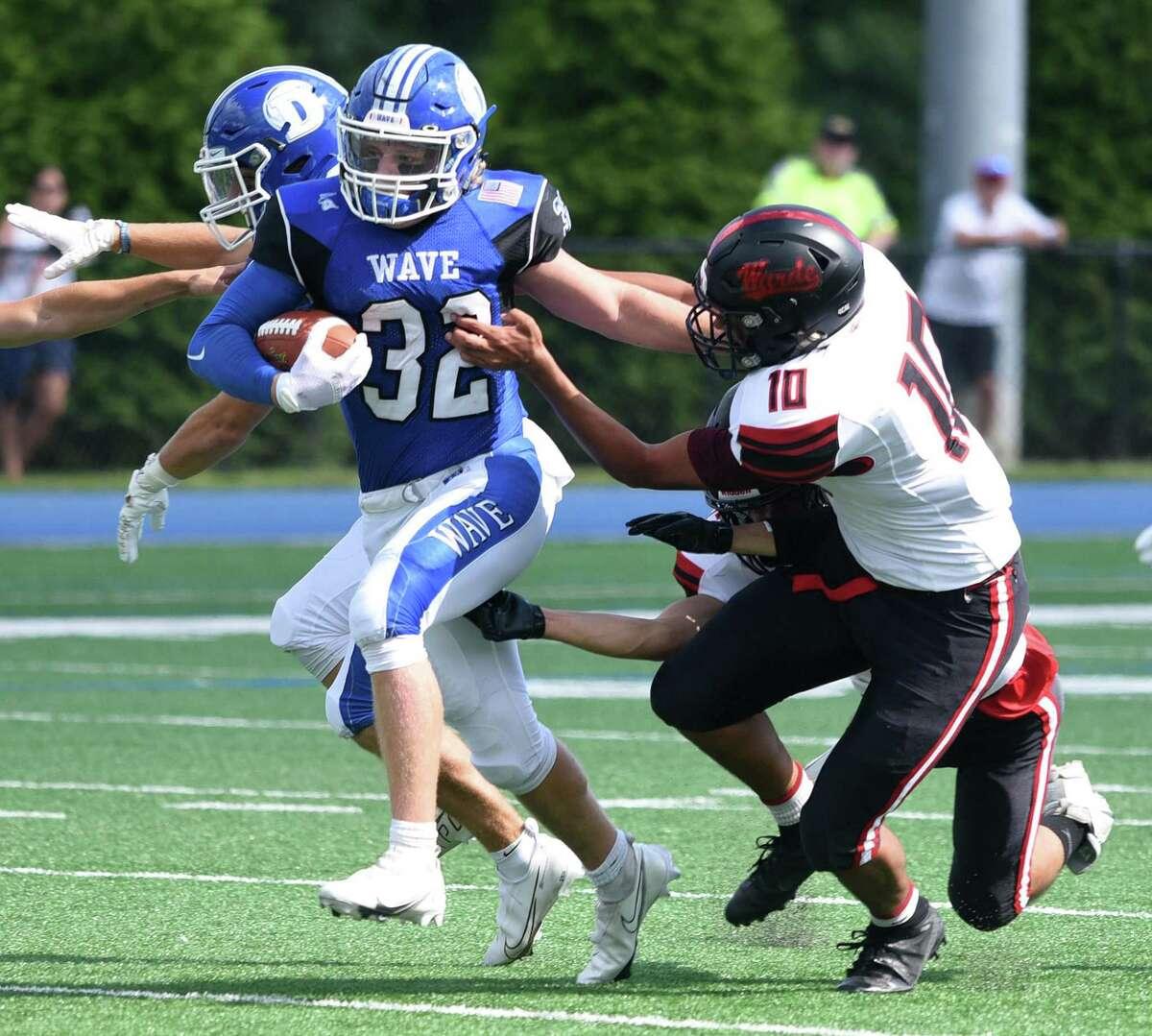 Darien running back Tighe Cummiskey (32) battles Warde's Anwar Sakly (10) during a football game at Darien High School on Sat., Sept. 11, 2021.