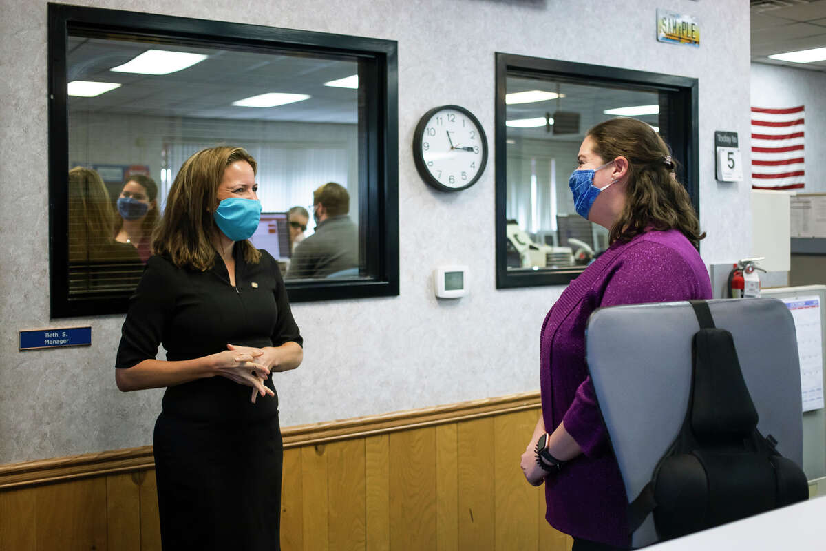 Michigan Secretary of State Jocelyn Benson, left, chats with Beth Sly, manager of the Midland branch office, right, during Benson's visit Tuesday, Oct. 5, 2021. (Katy Kildee/kkildee@mdn.net)