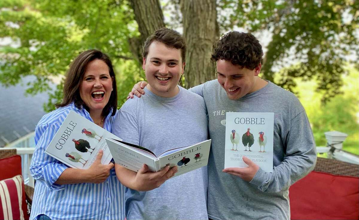 """The Isacs family holds copies of their Thanksgiving book, """"Gobble,"""" which releases in October."""