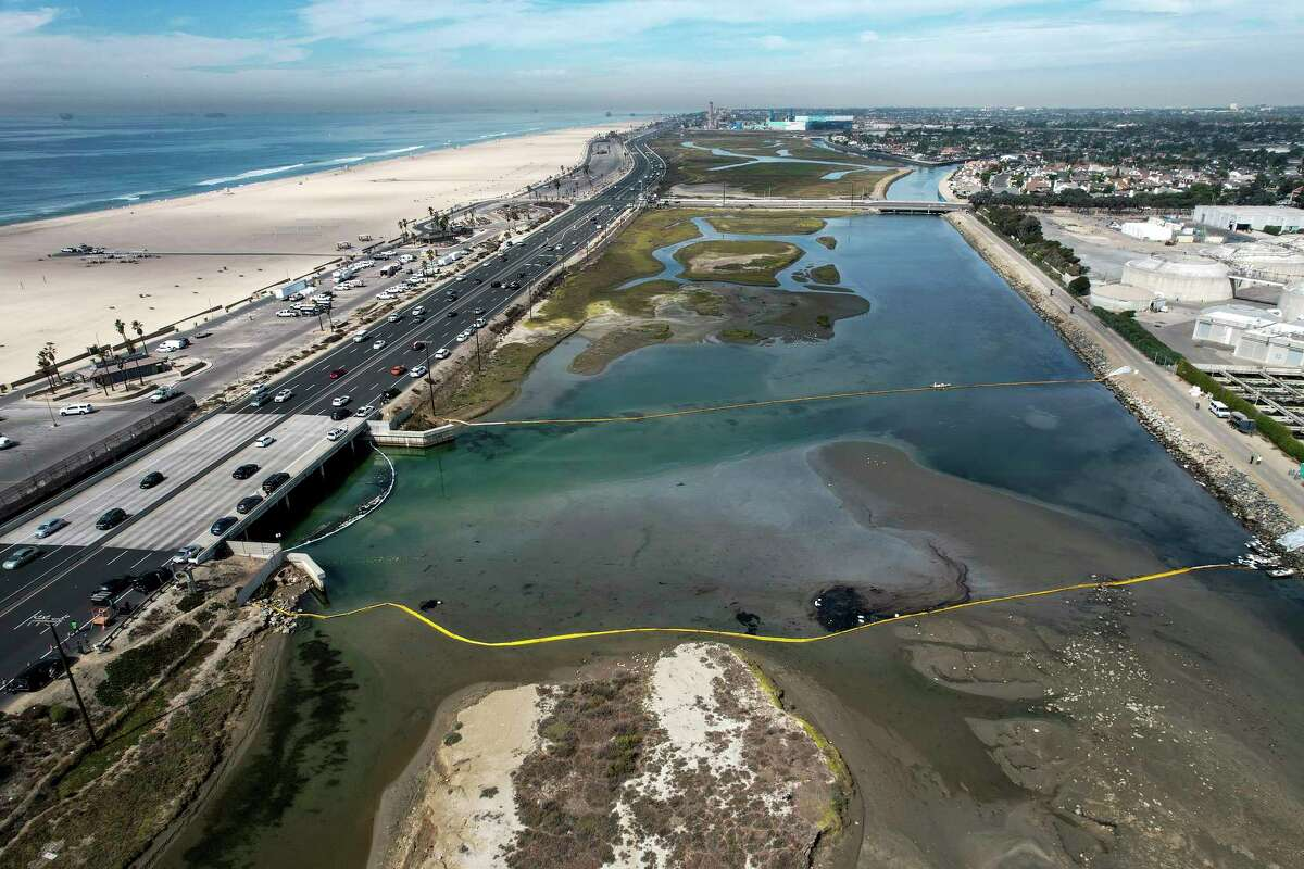 An aerial photo shows floating barriers known as booms to try to stop further incursion into the Wetlands Talbert Marsh after an oil spill in Huntington Beach, Calif., on Huntington Beach, Calif., on Monday, Oct. 4, 2021. A major oil spill off the coast of Southern California fouled popular beaches and killed wildlife while crews scrambled Sunday, to contain the crude before it spread further into protected wetlands.