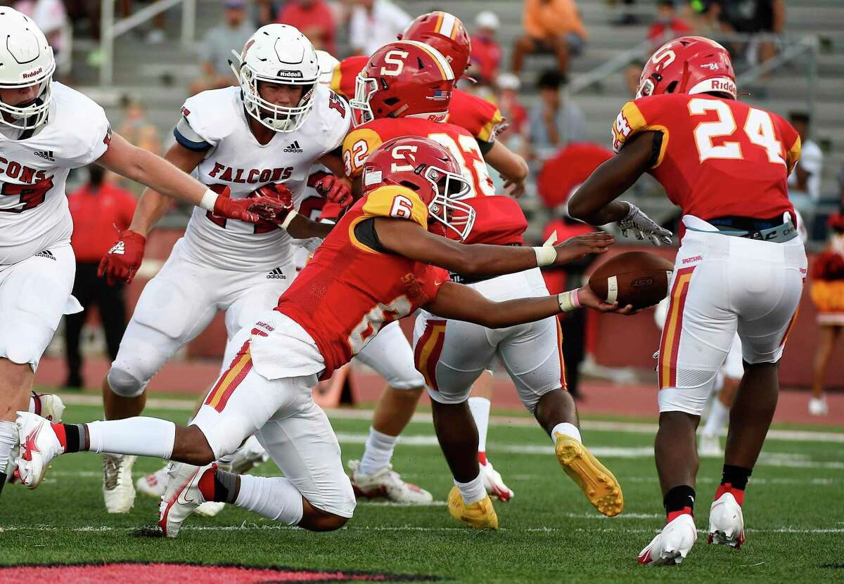 Stafford quarterback Brayden Baptiste slips while handing the ball off to running back Jamaal Wiley (24) during the first half of a high school football game against Huffman, Saturday, Aug. 29, 2020, in Stafford, TX. Wiley scored six touchdowns against Wharton in his most recent game.