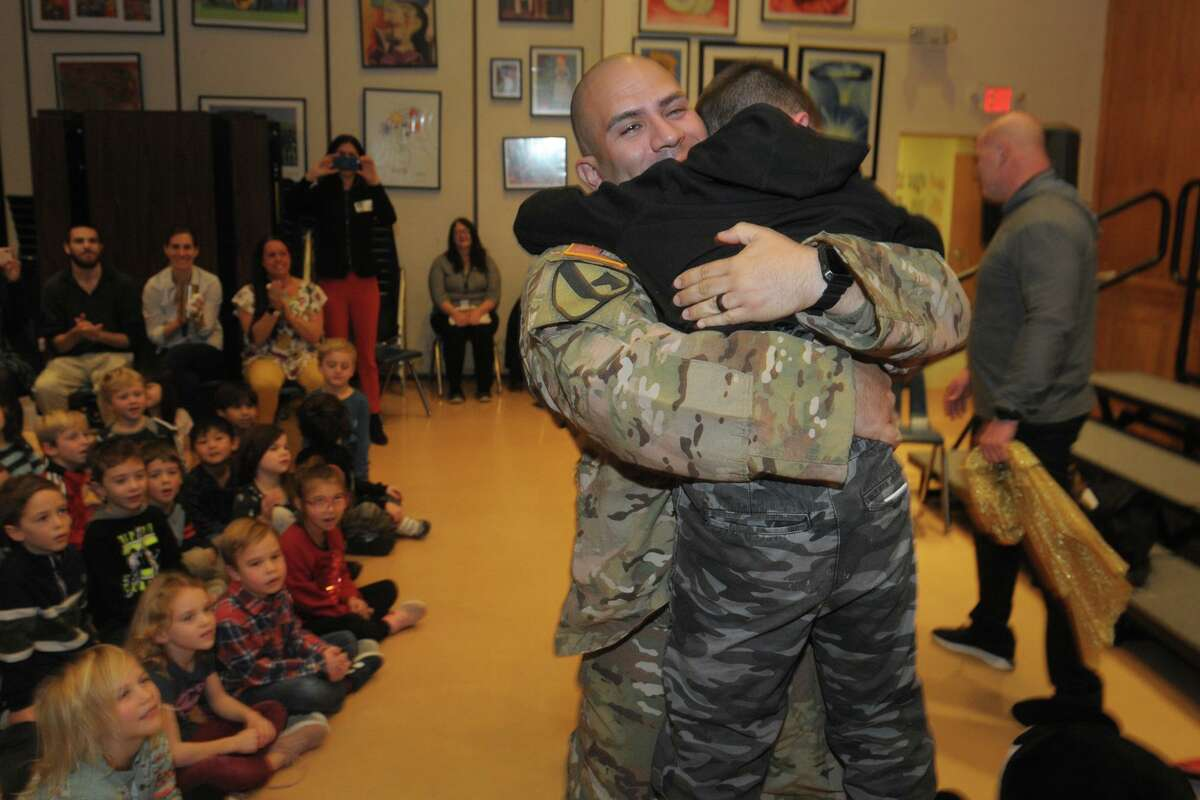 Fifth-grader Joshua Ochoa hugs his father, U.S. Army Staff Sgt. Joshua Ochoa, after a surprise meeting between the father and son during an assembly at Scotland Elementary School, in Ridgefield, Conn. Dec. 10, 2019.