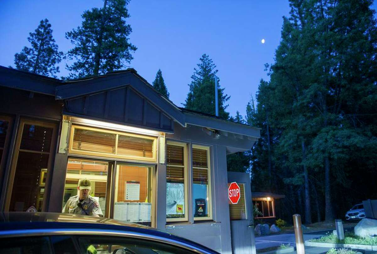 Park ranger James Topputo checks in a visitor at the Big Oak Flat entrance to Yosemite National Park. The park has done away with its reservation system, which took effect during the pandemic.
