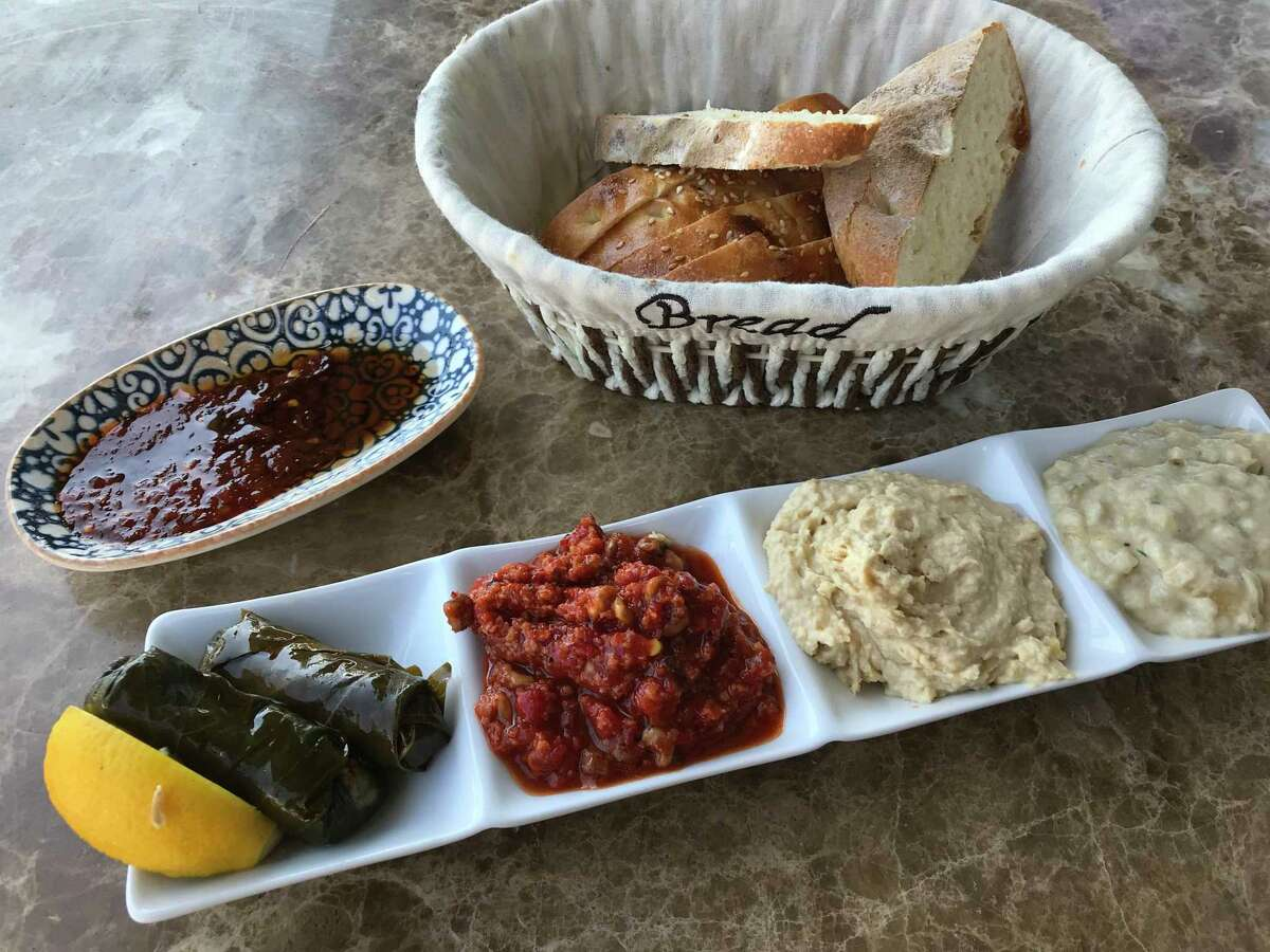 A sampler plate of Mediterranean appetizers including (from left) dolmas, mummara, hummus and baba ghanoush from Chef's Table Mediterranean Grill
