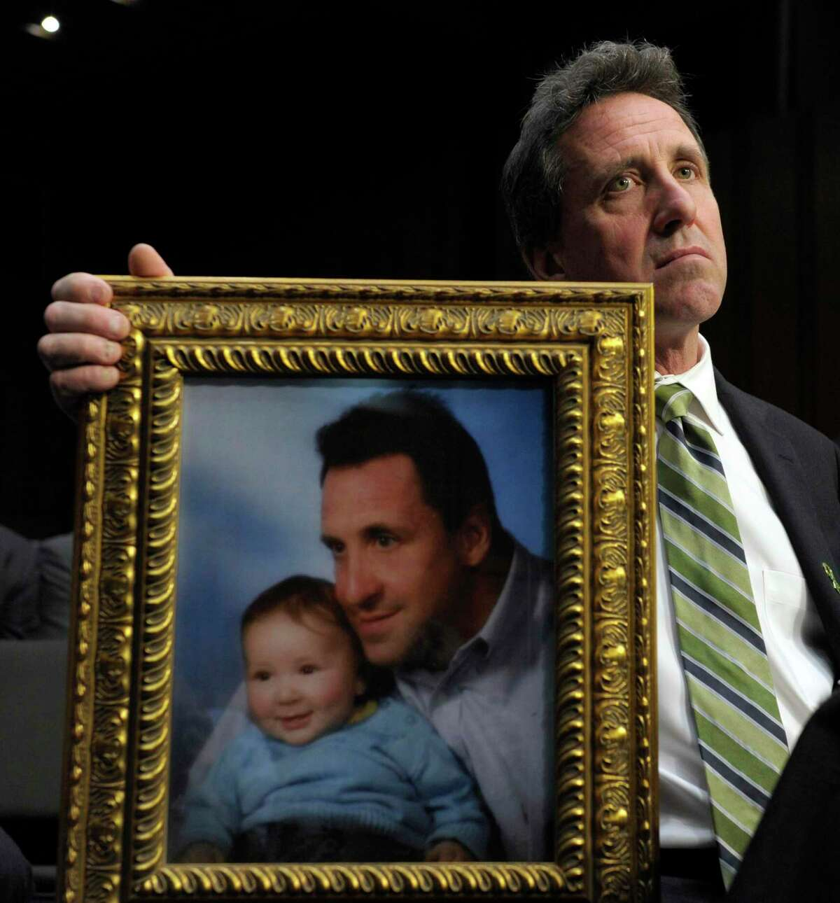 Neil Heslin, the father of a six-year-old boy who was slain in the Sandy Hook massacre in Newtown, Conn., on Dec. 14, 2012 holds a picture of himself with his son Jesse and wipes his eye while testifying on Capitol Hill in Washington, D.C. Heslin has won a defamation lawsuit against Alex Jones.
